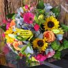 bright mix of fresh seasonal flowers. A vibrant bouquet or bunch wrapped in clear cello with a bow. By Eros Florist