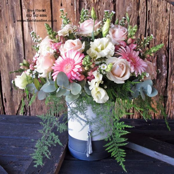 Classic pastel hat box arrangement of seasonal flowers, including roses