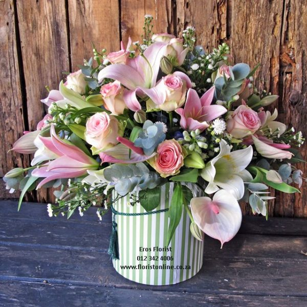 variety of pastel seasonal flowers in a classic hat box