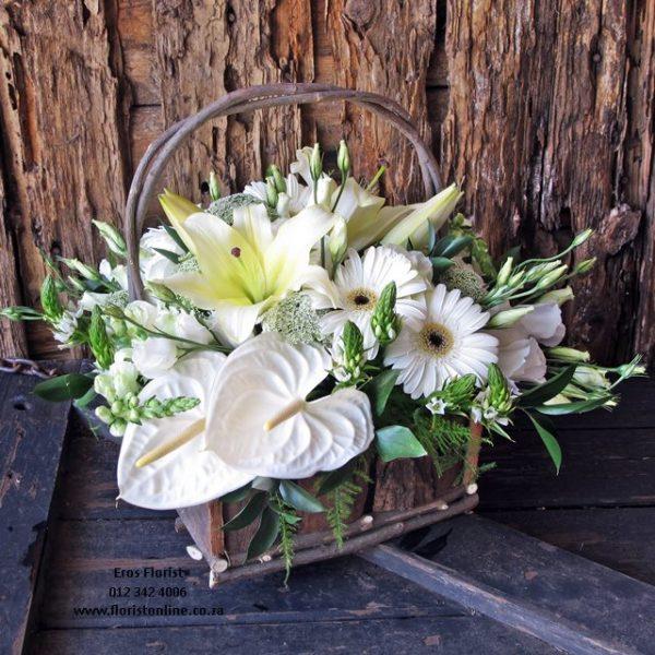 An overflowing floral flower basket in seasonal white flowers.